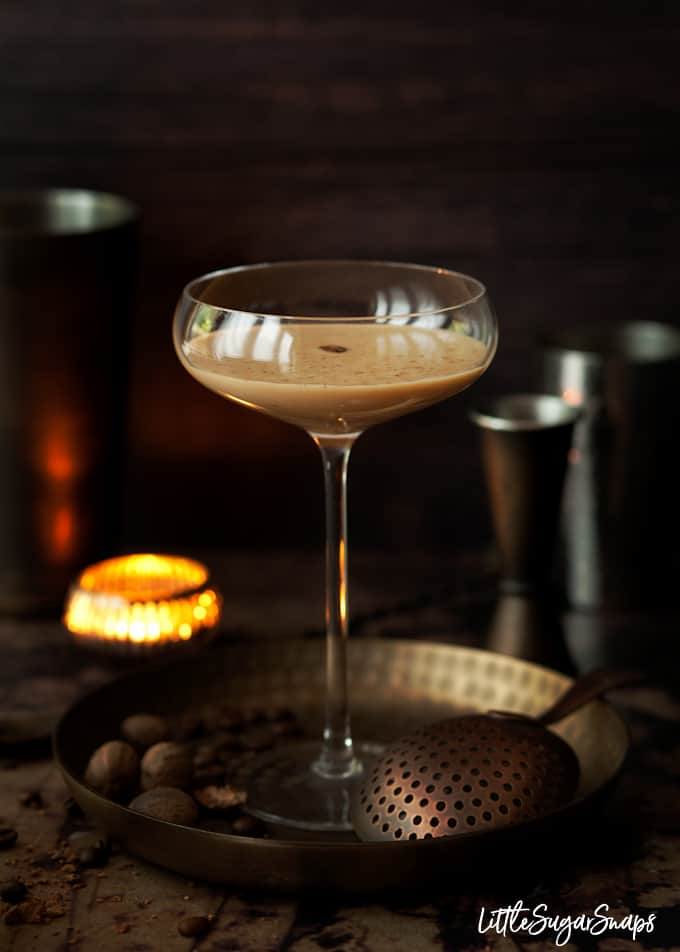 A Coffee Brandy Alexander cocktail in a tall glass, garnished with grated nutmeg and a coffee bean. it's on a letal tray with nutmeg and coffee beans nearly and a tealight in the background