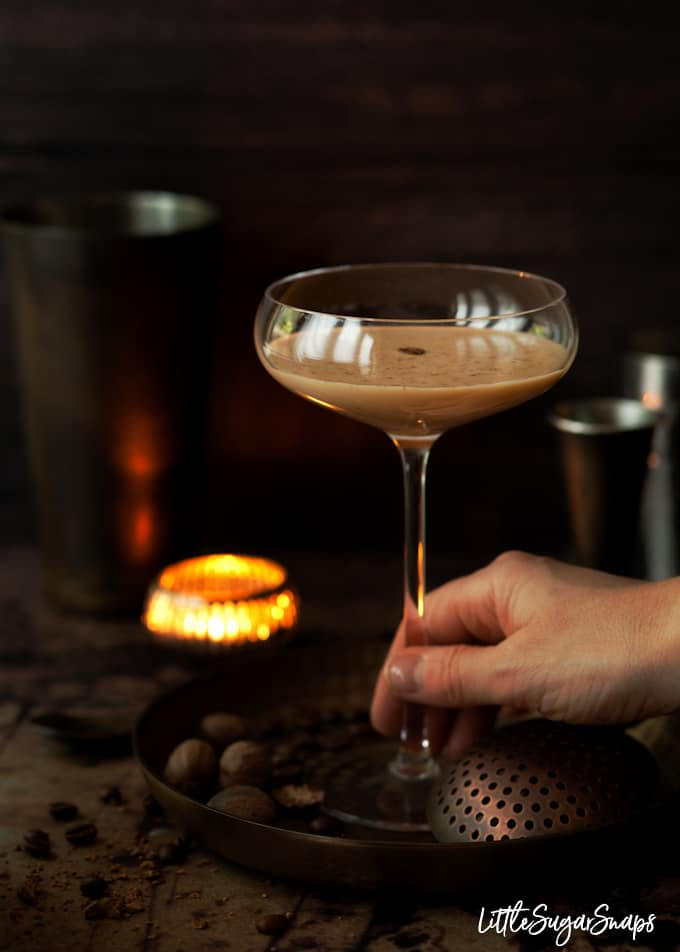 Person taking a cocktail glass filled with a creamy coffee cocktail. Cosy setting with a tealight in the background