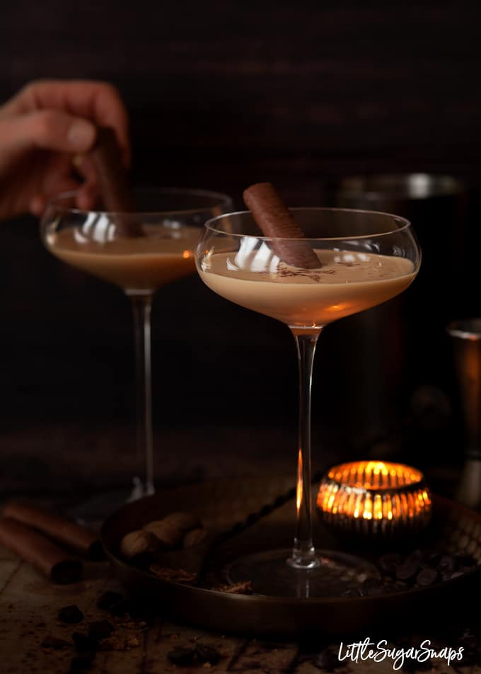 Person adding chocolate wafers to 2 creamy brandy alexander cocktails in tall cocktail glasses. Dark and cosy setting.