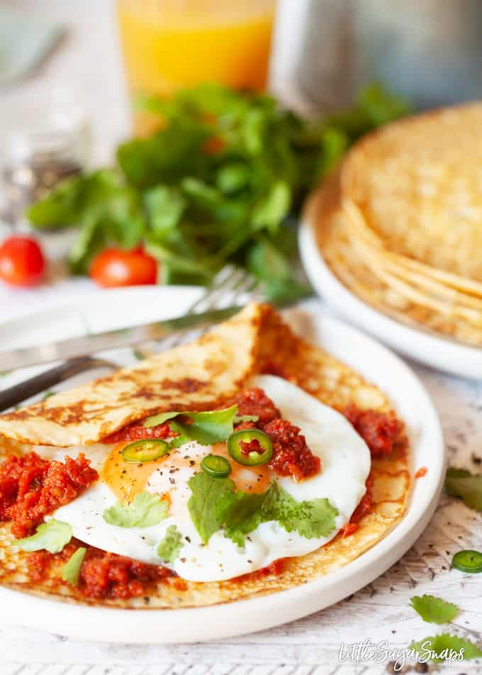 Huevos Rancheros cornmeal Crepes with spicy tomato sauce, a fried egg, green chillis and coriander.