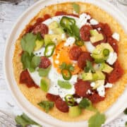 Huevos Rancheros with a cornmeal Crepe with spicy tomato sauce, a fried egg, green chillis and coriander plus chorizo, feta cheese and avocado chunks