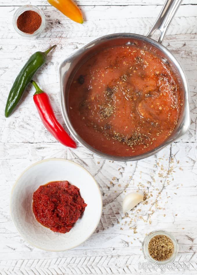 Cooked tomato salsa in a bowl and a pan with uncooked ingredients.
