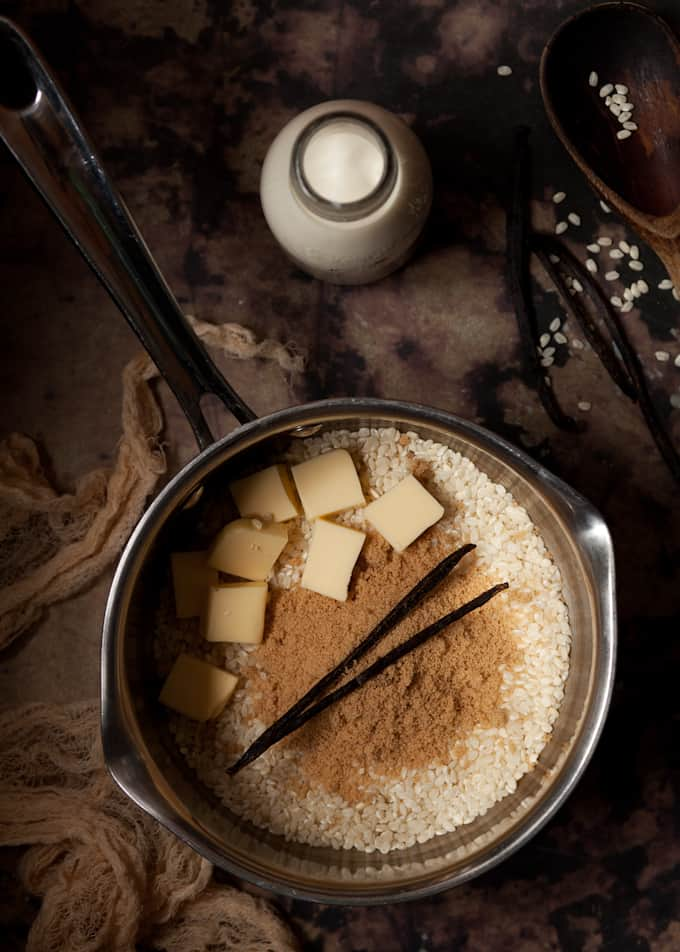 Ingredients in a pan - short grain rice, butter, brown sugar and vanilla pod.