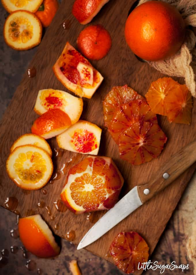 Blood oranges being de-pithed on a wooden chopping board