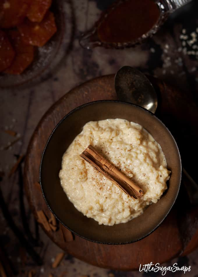 Rice pudding in a dark bowl with a cinnamon stick and grated cinnamon.