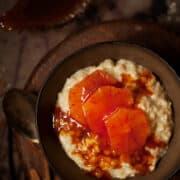 A bowl of dessert rice pudding topped with slices of blood orange and caramel sauce
