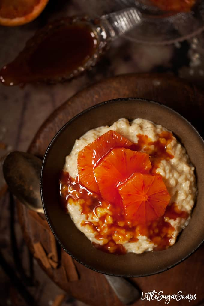 a bowl of rice pudding topped with blood orange slices in caramel sauce with chunks of cinnamon in the background