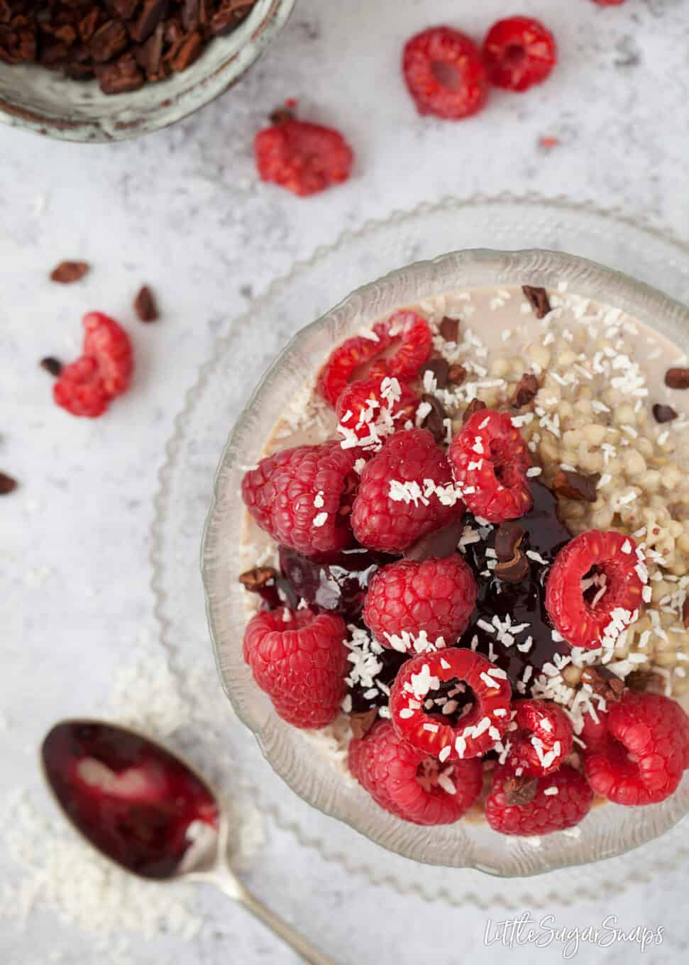 A bowl of buckwheat porridge with fruit compote, raspberries, cacao nibs and coconut