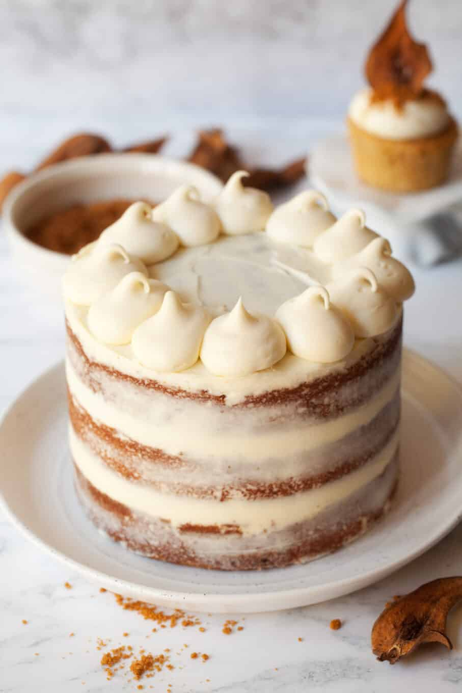 Piping mascarpone frosting onto a naked biscoff cake