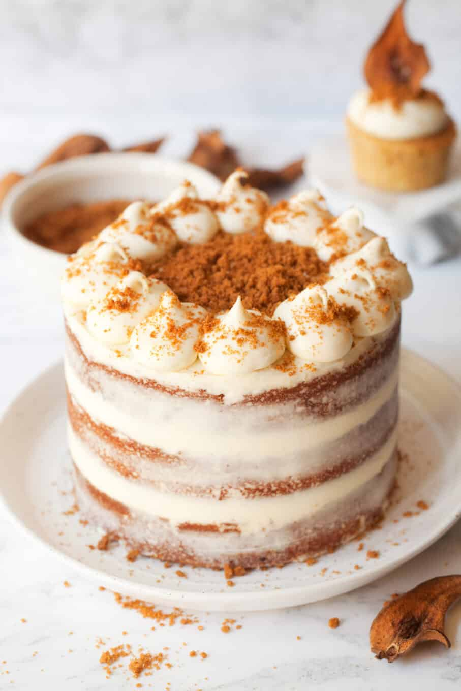 sprinkling biscuit crumbs onto a biscoff cake