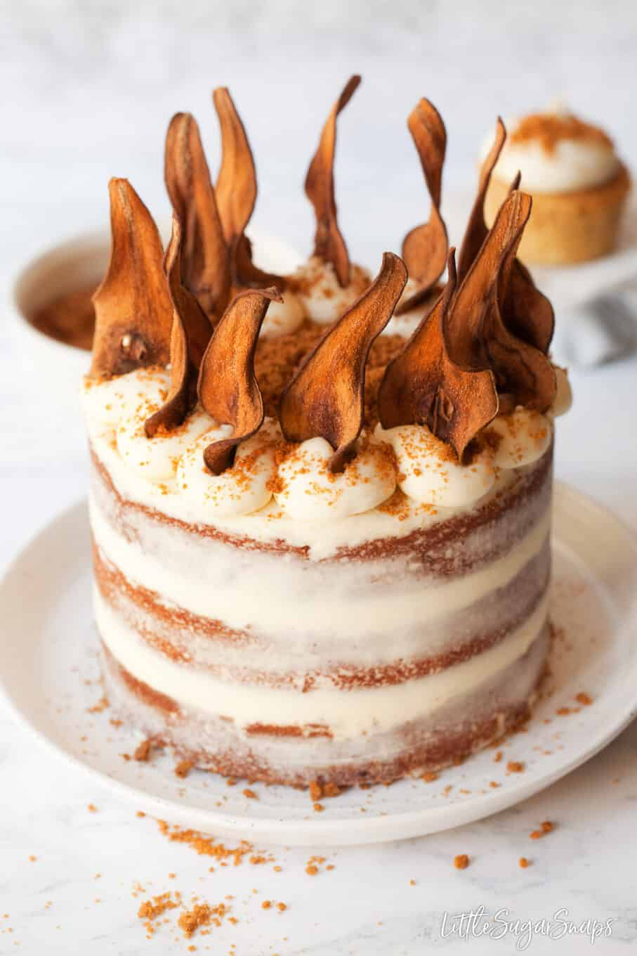 Naked biscoff cake decorated with mascarpone frosting, cookie crumbs and pear wafers