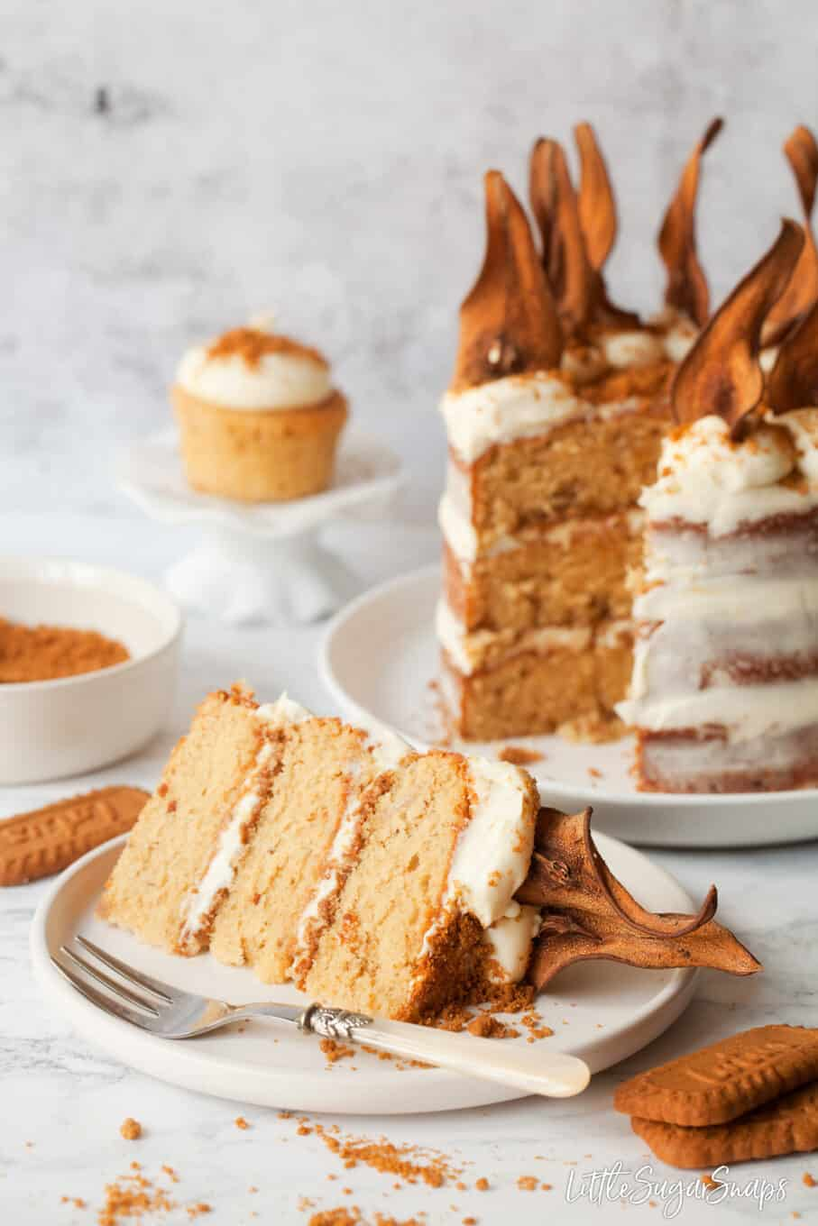 A slice of Biscoff cake on a plate with the cut cake behind. Revealing layers of sponge cake, biscoff spread and white chocolate frosting. Biscoff biscuits in the foreground and a cupcake behind