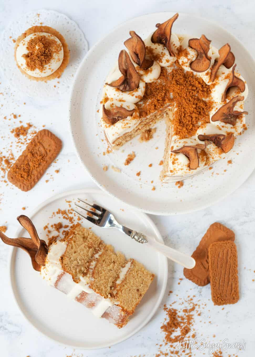 Top view of cut into pear cake recipe with mascarpone frosting, cookie crumbs and pear wafers
