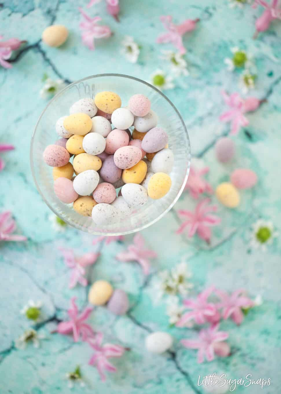 Chocolate mini eggs in a glass bowl against a blue background with spring flowers in shot.
