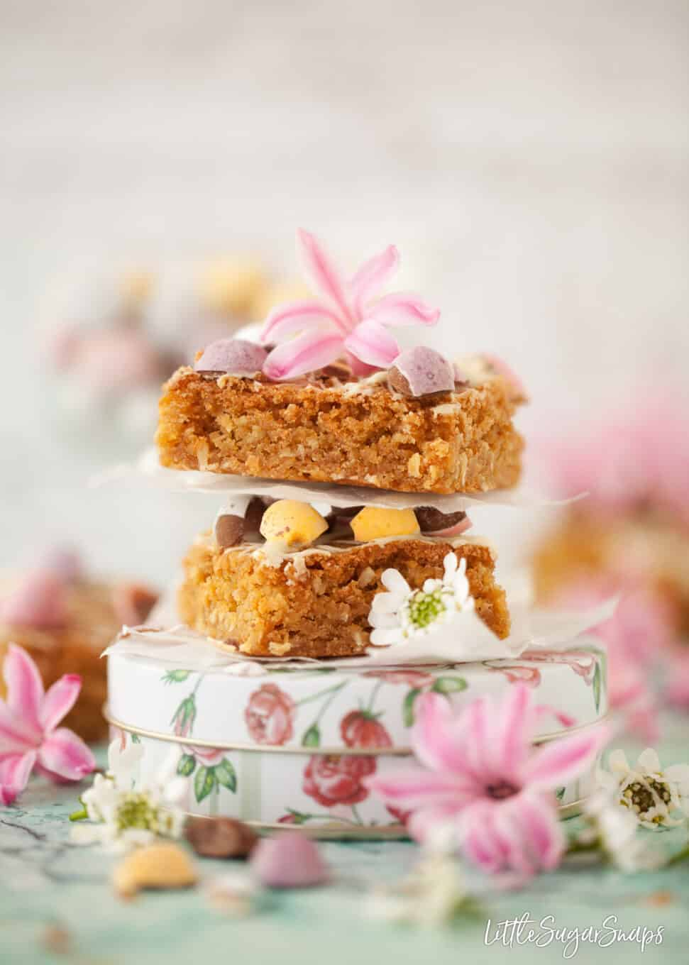 Squares on brown butter blondies with coconut stacked on top of each other and resting on a pretty floral tin. Pieces of mini eggs and spring flowers around the shot
