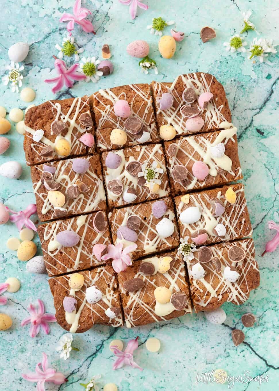 12 squares of freshly cut brown butter blondies with coconut with mini eggs on a blue board. Spring flowers around the image and spare mini eggs
