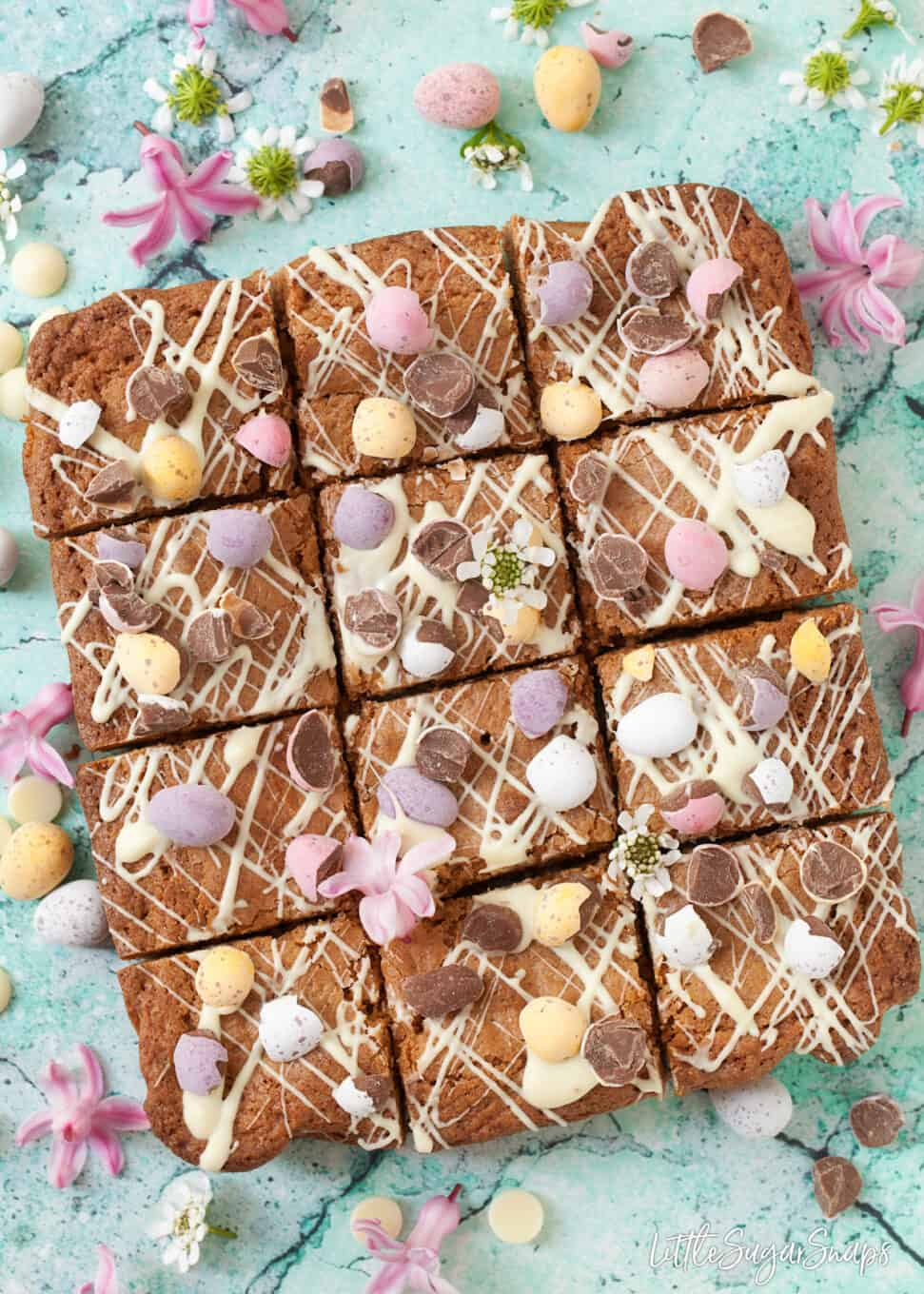 Freshly cut squares of Brown butter blondies with coconut. Decorated with white chocolate drizzle small easter eggs and spring flowers. On a blue worktop