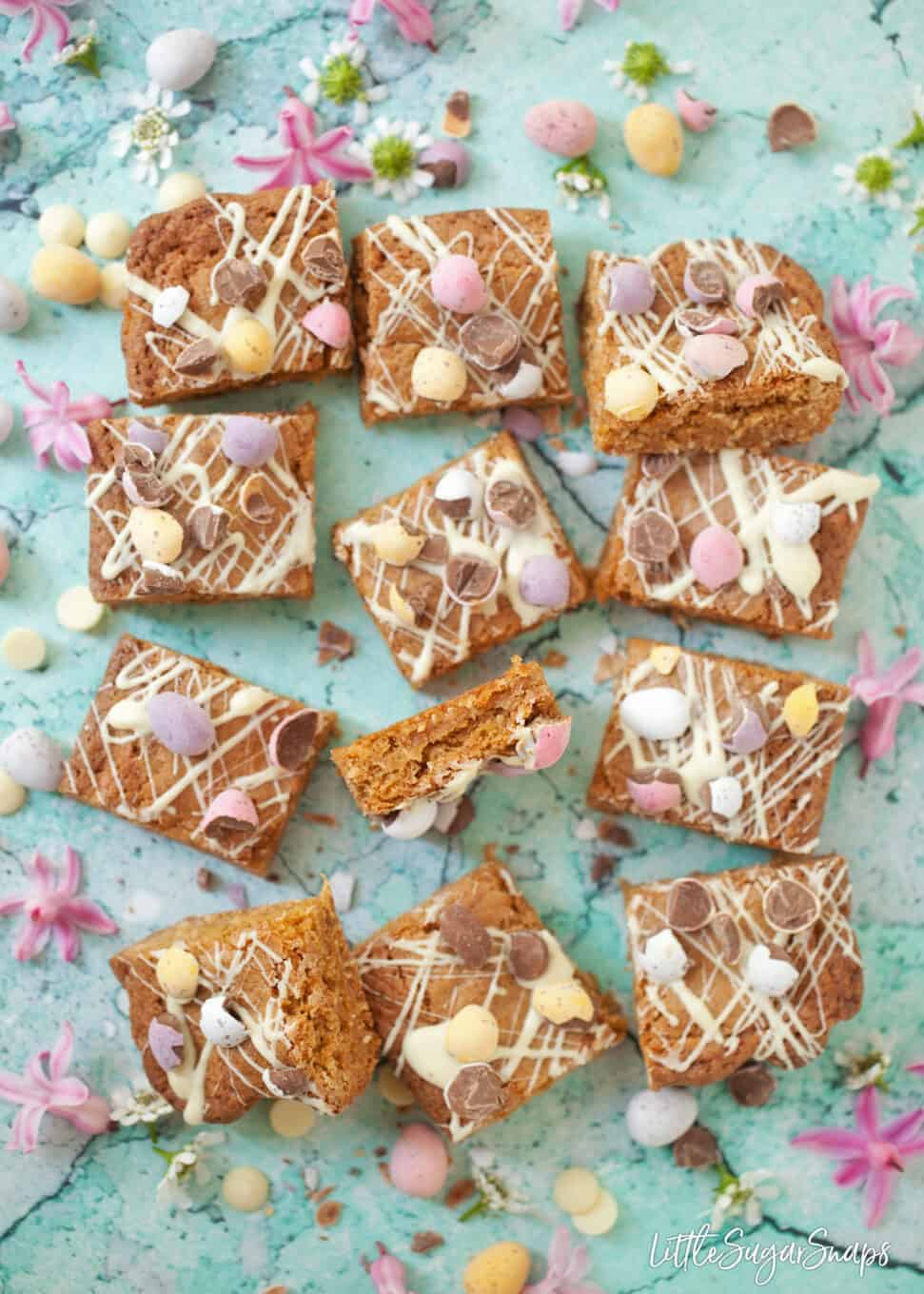 12 squares of Easter blondies topped with mini eggs and white white chocolate on a blue worktop. A few pink flowers, mini eggs and chocolate chips in shot