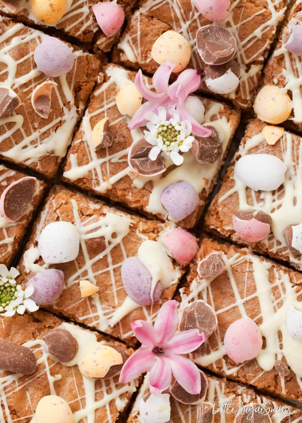 close up of easter blondies cut into squares with white chocolate drizzle and chopped mini eggs. A few flowers decorate them too