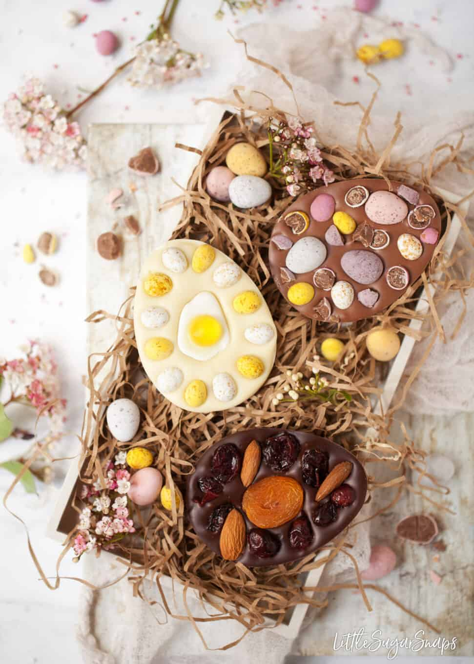 A tray of homemade easter eggs with flowers and chocolate mini eggs in the tray