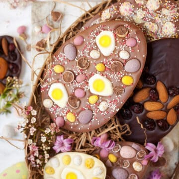 Homemade chocolate easter eggs decorated with fruit, nuts, jelly sweets and mini eggs