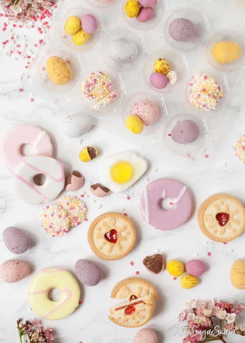 Miniature biscuits, chocolate eggs and sprinkles on a marble table top assembled for a homemade easter egg recipe