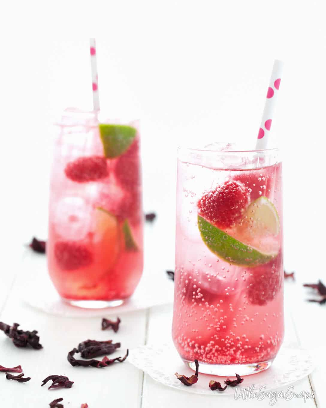 Sparkling hibiscus drink recipe served in tall glasses with raspberries and lime.