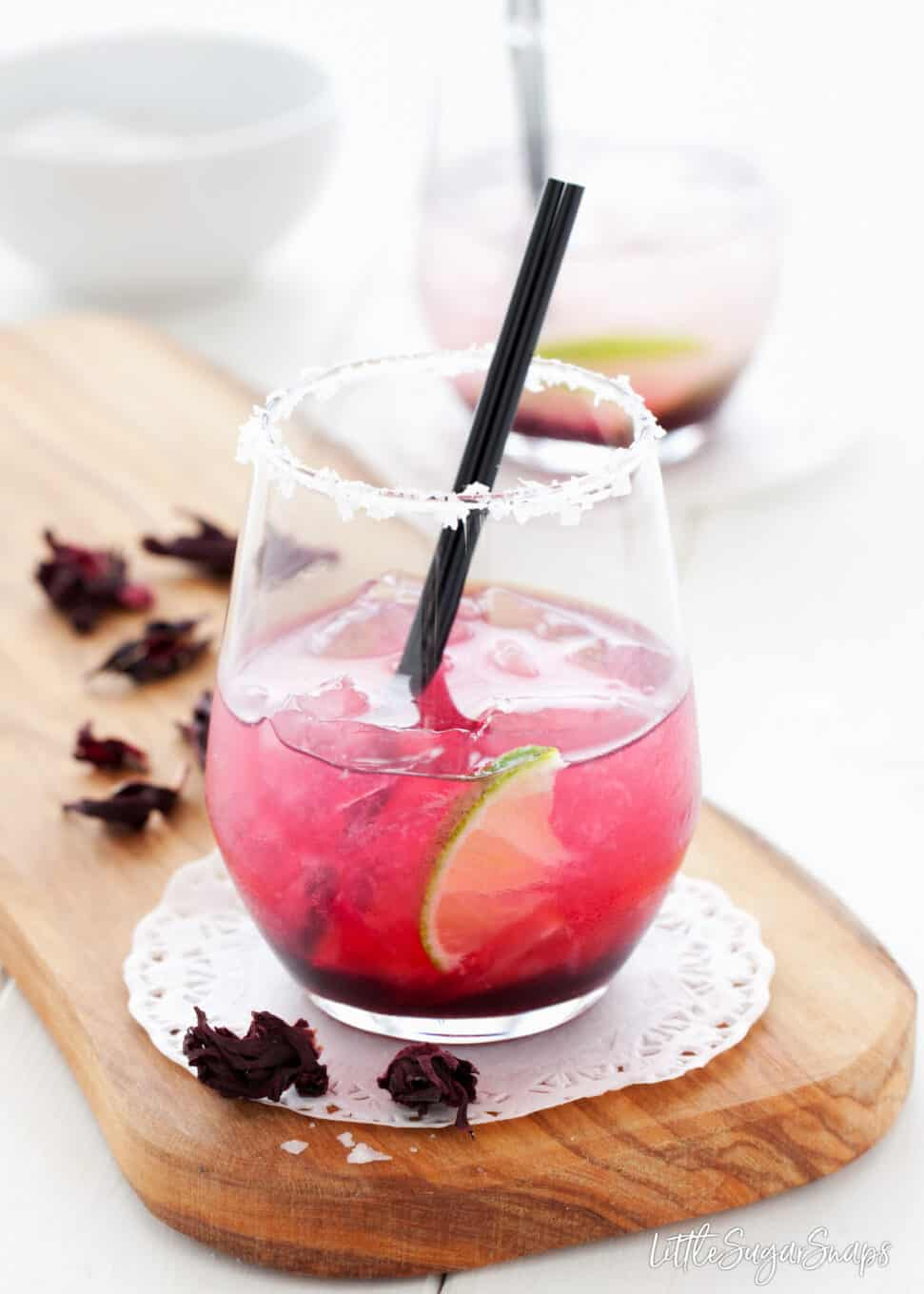 Hibiscus Margarita serve in a tumbler with ice, a lime wedge and a salt rim.