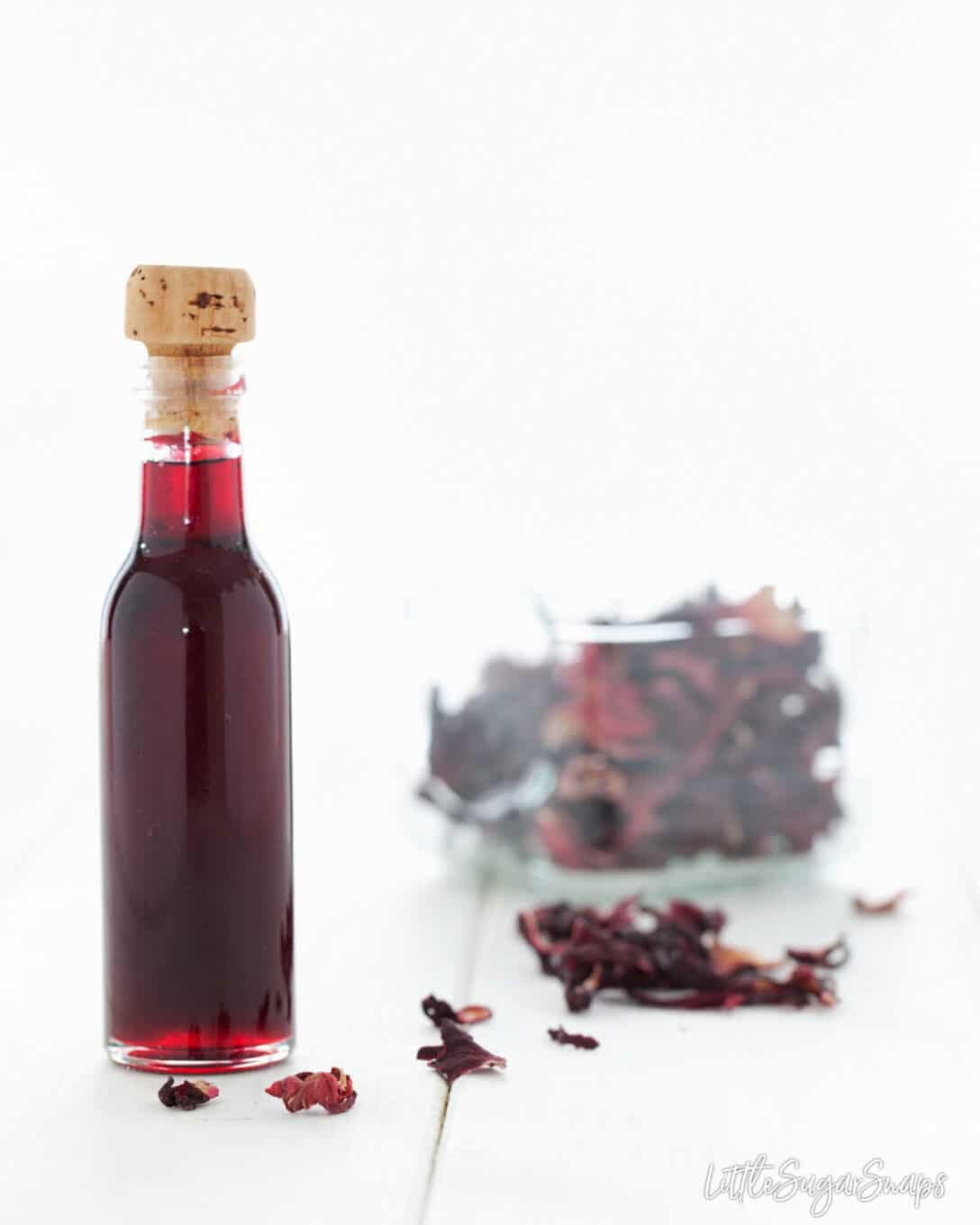 A bottle of homemade hibiscus syrup with dried flowers in the background