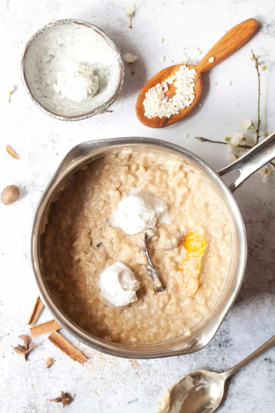 rice pudding in a pan with creamy ingredients being added