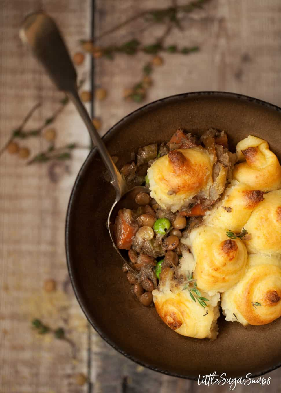 a bowl of vegan shepherd's pie with lentils - close up shot with a spoon in the bowl
