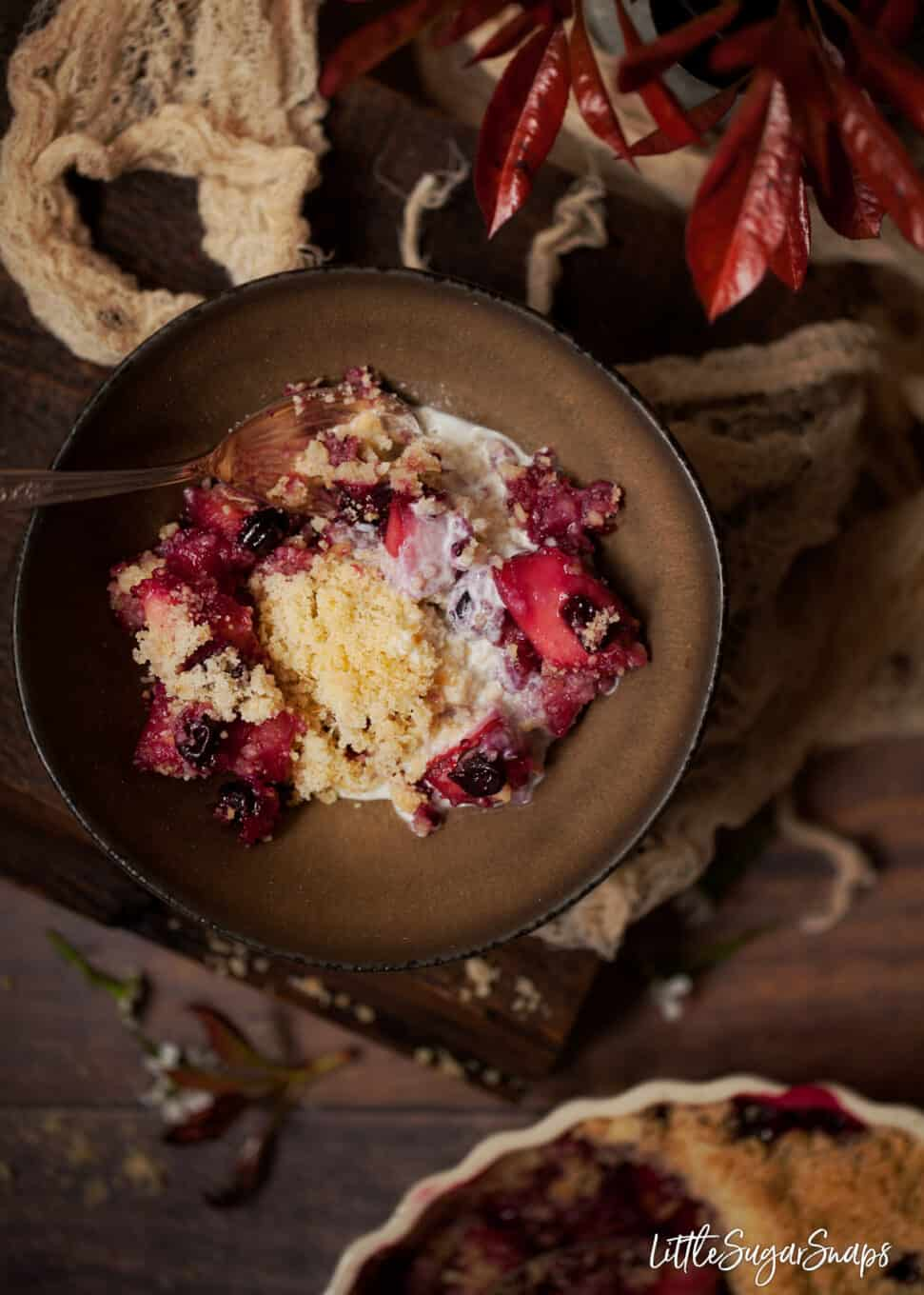 A bowl of blackcurrant crumble in a bowl with single cream poured over it. Rustic setting
