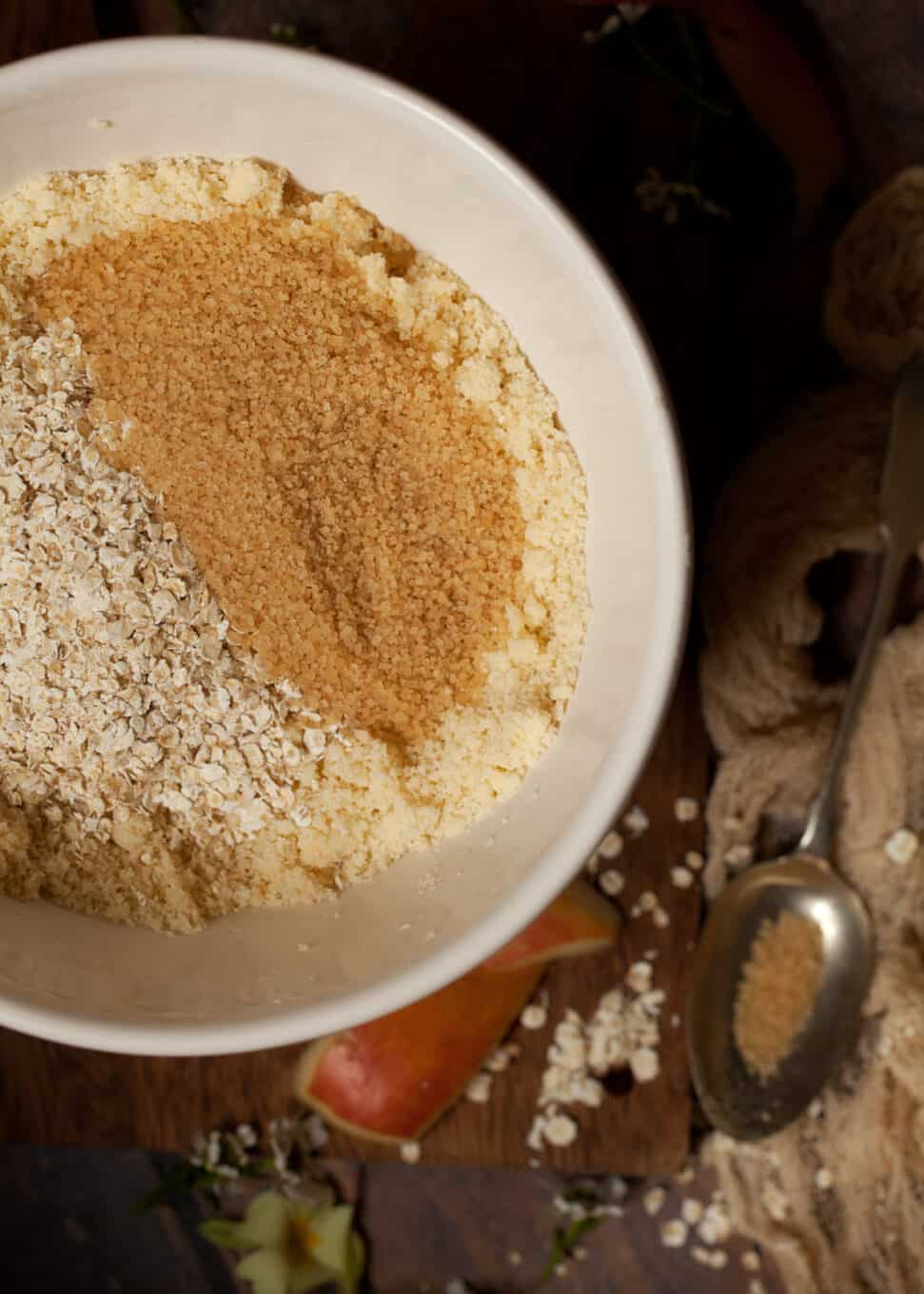oats and demerara sugar being added to crumble topping in a bowl