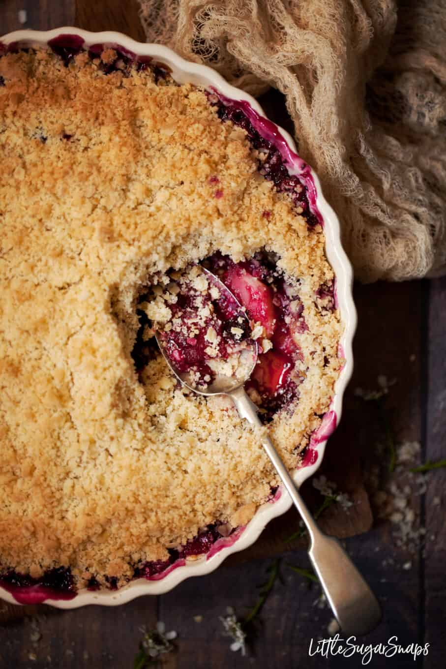 A serving dish filled with apple and blackcurrant crumble with a serving taken out and a spoon resting in the dish