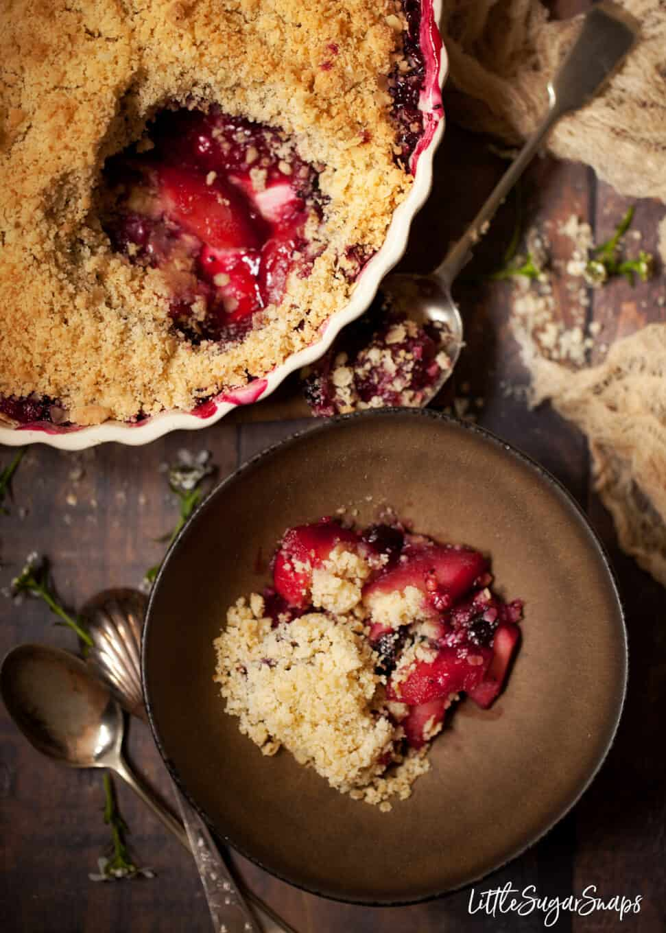 Blackcurrant crumble with apple served from a large round oven dish into a bowl. Rustic setting with wild flowers on the tablet top