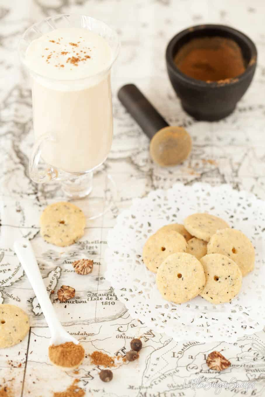 A chai latte with a few miniature biscuits on a paper doiley. A pestle and mortar in the background and a few spices within shot.