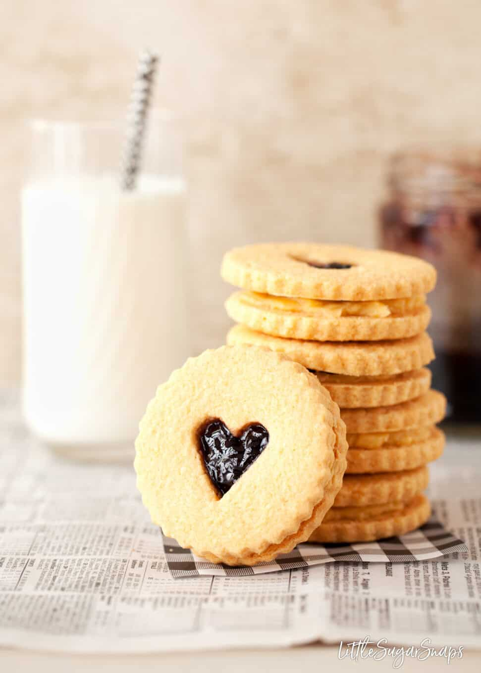 Biscuits made from a custard creams recipe and filled with custard cream filling and jam. Stacked up next to a glass of milk with one on it's side in front of the stack