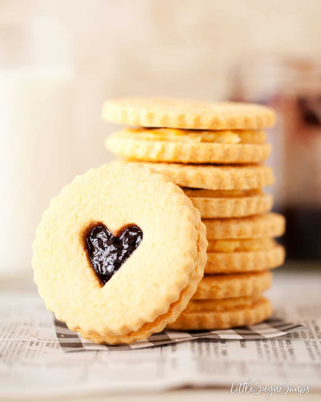 A stack of Custard Creams Biscuits with jam in the middle too. A love heart is cut out of one biscuit that is one it's side facing the camera angle.