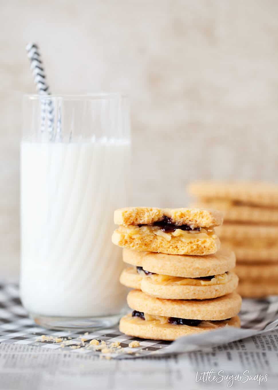 Custard creams biscuits stacked next to a tall glass of milk.