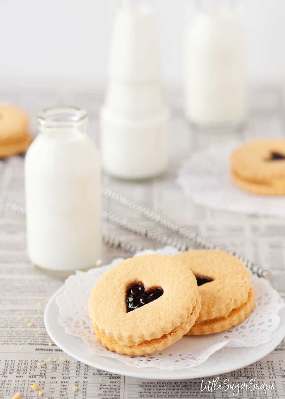 Jammie Dodger cookies on a small plate with mini bottles of milk