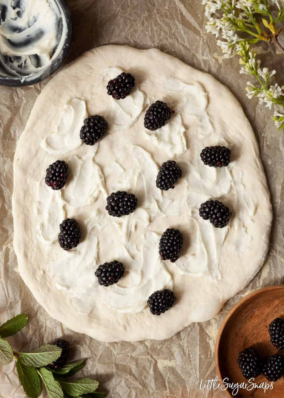 Blackberries scattered onto sweetened mascarpone cheese spread on a pizza base
