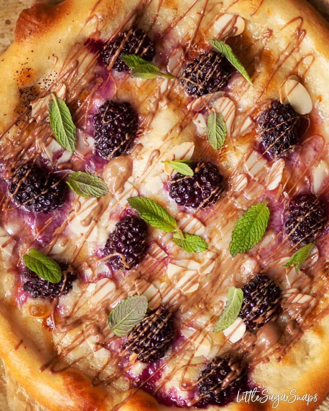 close up of dessert pizza with mascarpone, roasted fruit, chocolate, almonds and mint.