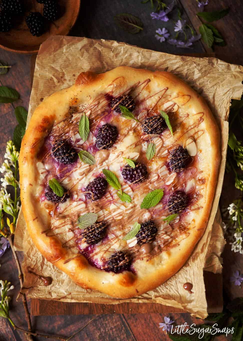 Sweet pizza topped with mascarpone, blackberries, milk chocolate drizzle, almonds and mint leaves.