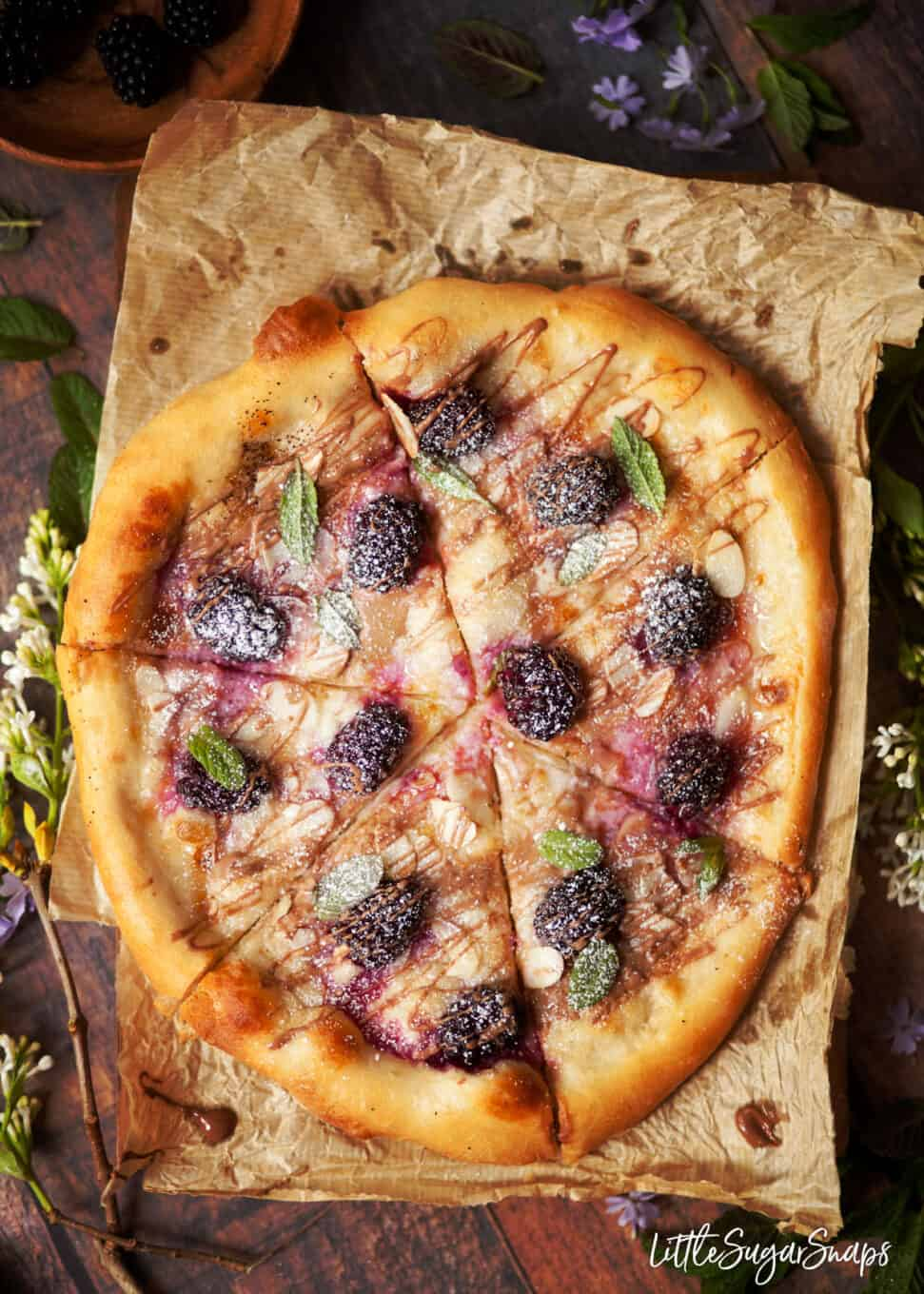 Sweet pizza with mascarpone and roast berries sliced into triangles.