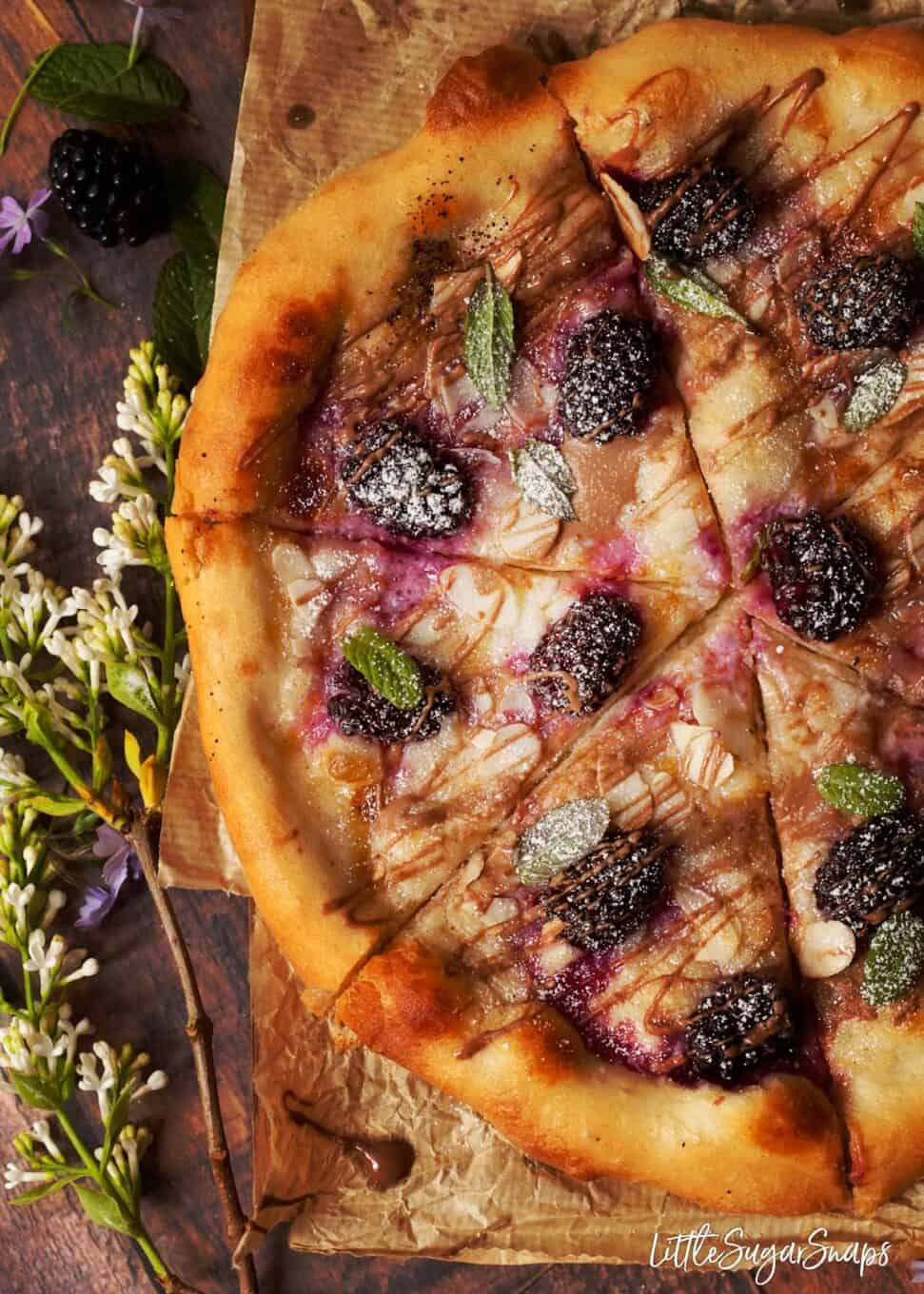 Overhead view of recipe for dessert pizza topped with soft cheese and berries.