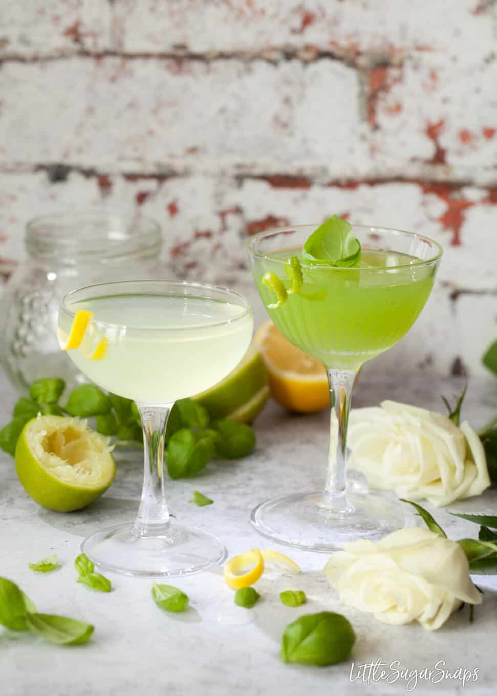 Classic Spring Feeling and Basil Cocktails garnished with lemon and lime. Ingredients and white roses on the worktop