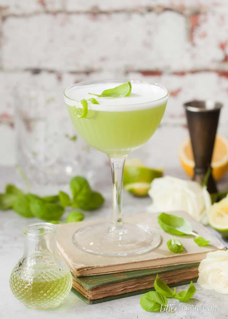 Variation on a spring feeling cocktail - green chartreuse cocktail is garnished with egg white foam and lime zest