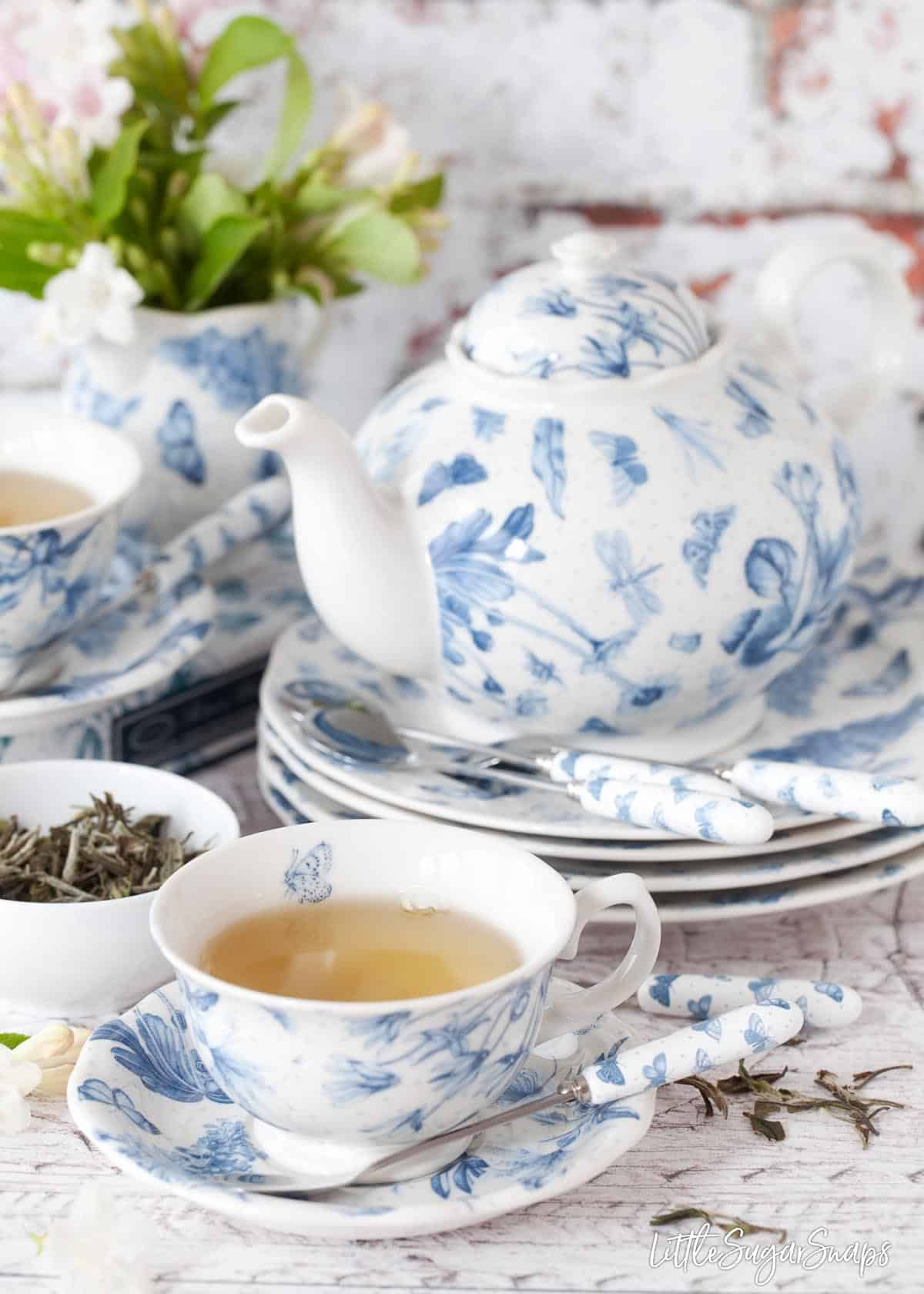 Serving afteroon tea: a cup of tea with a teapot in the background.