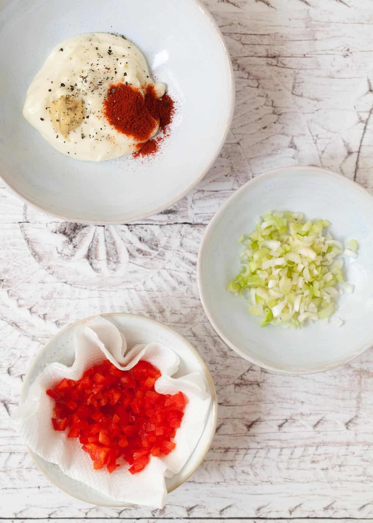 bowls of chopped salad onions, red pepper and mayonnaise