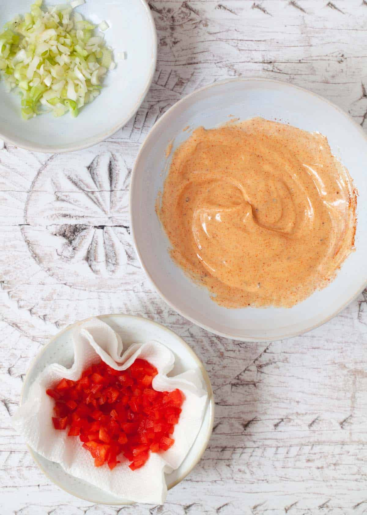 Paprika mayonnaise mixed in a shallow bowl with onion and red pepper alongside